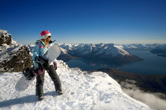 Snowboard girl. Woman with snowboard standing on top of snowy mountain royalty free stock image