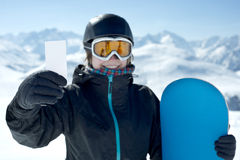 Snowboard girl with blank card smiling. Winter Sport girl holding skipass and snowboard smiling. Concept to illustrate ski admission fee Stock Image