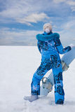 Snowboard girl in blue stay at the bottom of hill Royalty Free Stock Photo