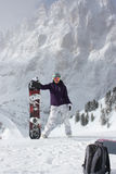 Snowboard girl. Young woman stand with her snowboard. Royalty Free Stock Image