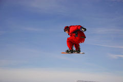 Snowboard Grab. A rider all dressed in red pops a big air and grabs his board Stock Photos