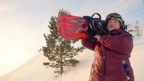 Snowboard idoso da terra arrendada do snowboarder da mulher em ombros na montanha nevado video estoque