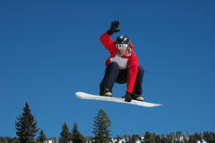 Snowboard Jump 1. A snowboarder sticks out his tounge as he flys through the air