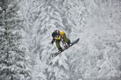 Snowboard jump. Young boys jumping in air ind showing trick with snowboard at winter season Stock Photography