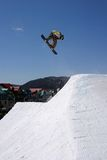 Snowboard jump on blue sky. Snowboarder jumping with a rotation over a spine jump and grabing his board over a blue sky and buildings and mountains Stock Image