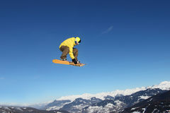 Snowboard jump. Man flying on a snowboard in the Alps. Sunny day in The Moon Park. Meribel ski resort in France royalty free stock images