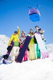 Snowboard mates on ski resort. Happy friends men and women stand in snow holding snowboards lifting and waving hands and cable car ski lift Stock Photo
