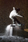 Snowboard Night Storm Slide. A snowboarder slides a rail at night during an intense snow storm Royalty Free Stock Image