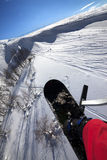 Snowboard over off-piste slope in sun day Stock Photography