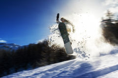 Snowboard power. Powerful image of a snowboarder jumping over a kicker in the backcountry powder Royalty Free Stock Images
