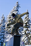 Snowboard Rail Slide. A snowboarder slides a rail at a ski area terrain park Royalty Free Stock Photo