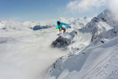 Snowboard rider jumping on mountains. Extreme snowboard freeride sport. Snowboard rider jumping on snowy mountains. Extreme snowboard freeride sport Royalty Free Stock Photography