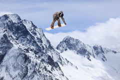 Snowboard rider jumping on mountains. Extreme freeride sport. Royalty Free Stock Image