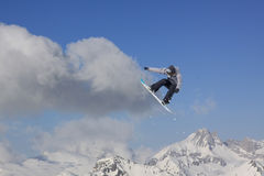 Snowboard rider jumping on mountains. Extreme snowboard freeride sport. Royalty Free Stock Photography