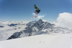Snowboard rider jumping on mountains. Extreme snowboard freeride sport. Royalty Free Stock Image