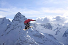 Snowboard rider jumping on mountains. Extreme snowboard freeride sport. Snowboard rider jumping on winter mountains. Extreme snowboard freeride sport Stock Photography