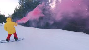 Snowboard rider with smoke bomb on mountain slope. Action extreme sports camera shot of professional awesome snowboarder in bright colorful outfit ride, spin and stock video footage