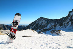 Snowboard. A snowboard with a snowy mountains behind stock images
