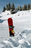 Snowboard stuck in the snow. Red snowboard stuck in deep snow Royalty Free Stock Image