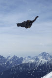 Snowboard trickster. A snowboarder jumps a corkscrew Stock Photography