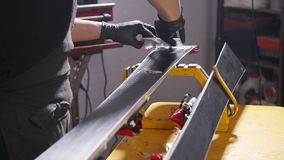 Ski or snowboard tuning and reapair concept. Winter shop worker doing base repair and service. Snowboard tuning and reapair. Winter shop worker doing base repair stock video