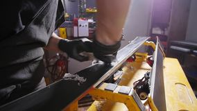 Ski or snowboard tuning and reapair concept. Winter shop worker doing base repair and service. Snowboard tuning and reapair. Winter shop worker doing base repair stock footage