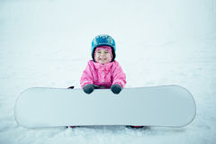 Snowboard Winter Sport. Little kid girl playing with snow wearing warm winter clothes. Royalty Free Stock Image