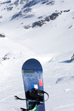 Snowboard on wintry mountain. Vertical snowboard on snowy mountainside in winter Stock Photos