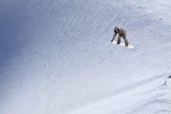 Snowboarder που πετά στο υπόβαθρο της χιονώδους κλίσης Ακραίος χειμερινός αθλητισμός, στοκ εικόνες
