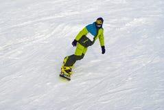 Snowboarder ślizga się puszek przeciw tłu śnieg skłon Fotografia Royalty Free