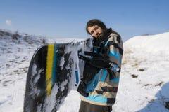 Snowboarder με μια μακρυμάλλη εκμετάλλευση ένα σνόουμπορντ όπως ένα πυροβόλο όπλο Ακραίος χειμερινός αθλητισμός στοκ φωτογραφία με δικαίωμα ελεύθερης χρήσης