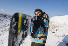 Snowboarder με μια μακρυμάλλη εκμετάλλευση ένα σνόουμπορντ όπως ένα πυροβόλο όπλο Ακραίος χειμερινός αθλητισμός στοκ εικόνες