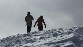 Snowboarder με το σνόουμπορντ που περπατά στο χιονώδες βουνό στην αιχμή Snowboarder που αυξάνεται επάνω στη χιονώδη αιχμή βουνών  απόθεμα βίντεο