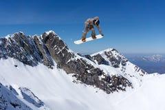 Snowboarder που πηδά στα βουνά Ακραίος αθλητισμός freeride σνόουμπορντ Στοκ Εικόνες
