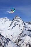 Snowboarder που πηδά στα βουνά Ακραίος αθλητισμός freeride σνόουμπορντ Στοκ εικόνες με δικαίωμα ελεύθερης χρήσης