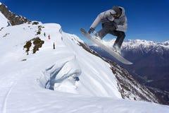 Snowboarder που πηδά στα βουνά Ακραίος αθλητισμός freeride σνόουμπορντ Στοκ εικόνα με δικαίωμα ελεύθερης χρήσης