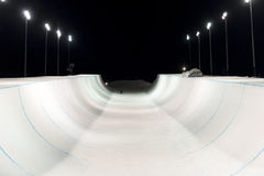 Snowboarder σε ένα χιόνι halfpipe τη νύχτα αναμμένο επάνω από τα φω'τα Στοκ εικόνες με δικαίωμα ελεύθερης χρήσης