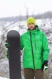 Snowboarder στα φωτεινά ενδύματα που θέτουν με ένα σνόουμπορντ Στοκ εικόνα με δικαίωμα ελεύθερης χρήσης
