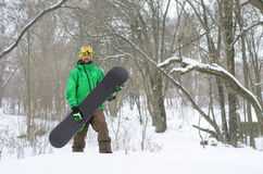 Snowboarder στα φωτεινά ενδύματα που θέτουν με ένα σνόουμπορντ Στοκ εικόνες με δικαίωμα ελεύθερης χρήσης