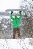 Snowboarder στα φωτεινά ενδύματα που θέτουν με ένα σνόουμπορντ Στοκ Εικόνες