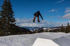 Snowboarder στη δράση: Άλμα στο βουνό Snowpark Στοκ εικόνα με δικαίωμα ελεύθερης χρήσης