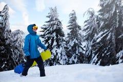 Snowboarder взбираясь к верхней части горы нося его сноуборд через лес для backcountry freeride и носить стоковое фото rf