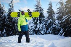Snowboarder взбираясь к верхней части горы нося его сноуборд через лес для backcountry freeride и носить стоковые фотографии rf