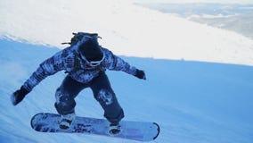 Snowboarder двигает вниз покрытый снег наклон горы сток-видео