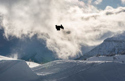 Snowboarder выполняя сальто с большой скачки в горах Стоковое Изображение RF