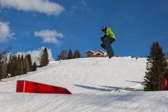 Snowboarder в действии: Скакать в гору Snowpark Стоковое Фото