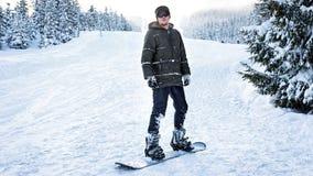 Snowboarder в стеклах лыжи стоит на сноуборде в древесинах зимы на наклонах Стоковые Изображения