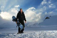 Snowboarder в черном костюме стоя на дороге Стоковые Изображения RF