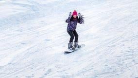 Snowboarder девушки спускает от гор в снеге на сноуборде Стоковые Изображения RF