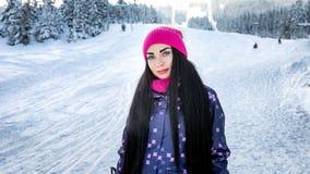 Snowboarder девушки стоя в зиме на наклоне лыжи усмехаясь и смотря Стоковое Фото